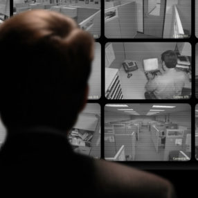 Man watching an employee work via a closed-circuit video monitor