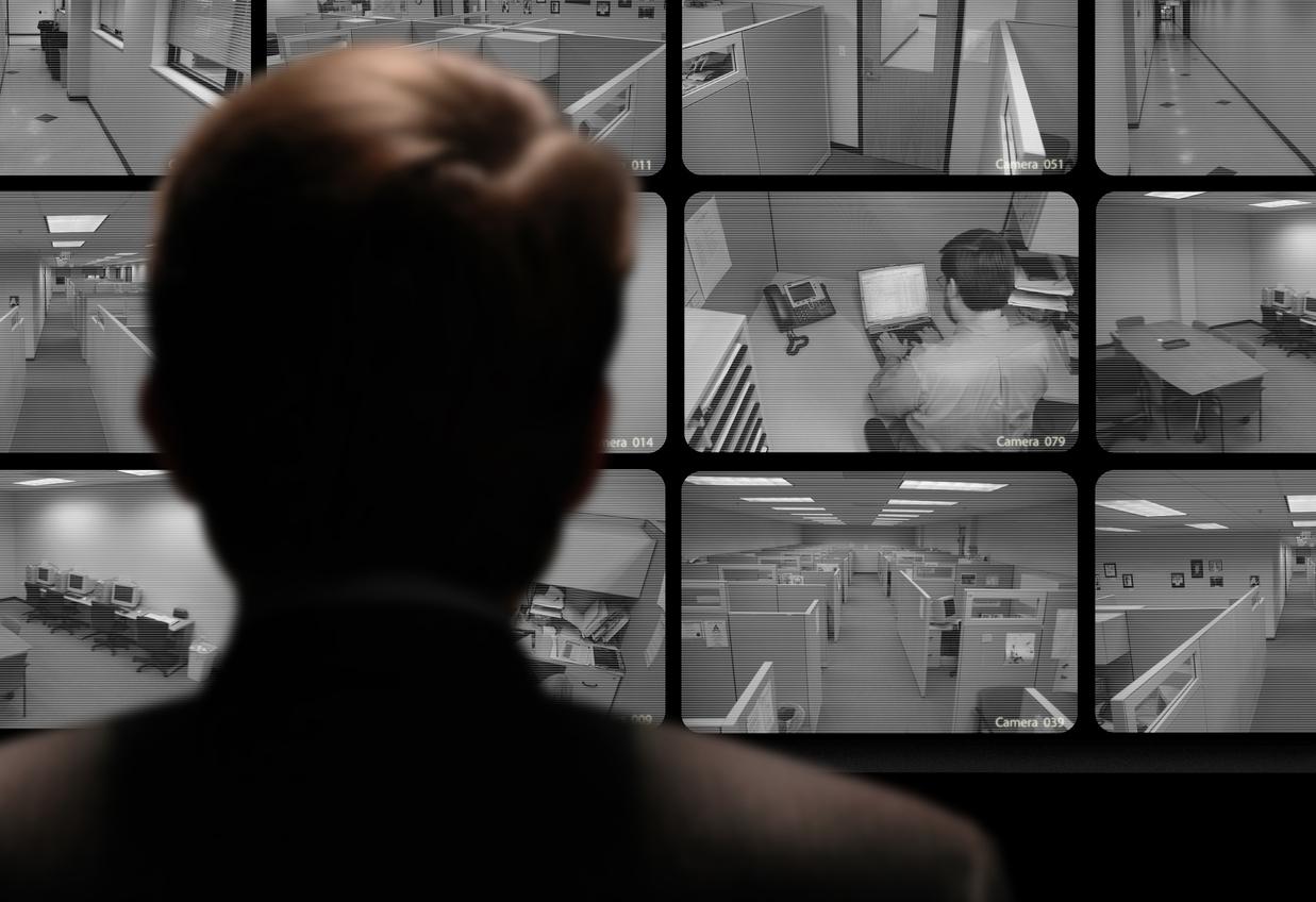 Man watching an employee work via a closed-circuit video monitor